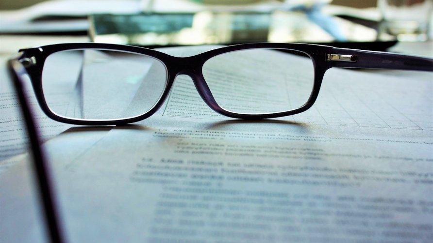 Zdjęcie przedstawia okulary leżące na dokumencie