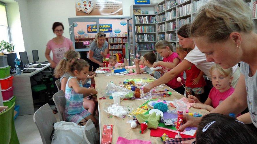 Zdjęcie przedstawia dzieci przy stołach podczas tworzenia prac plastycznych