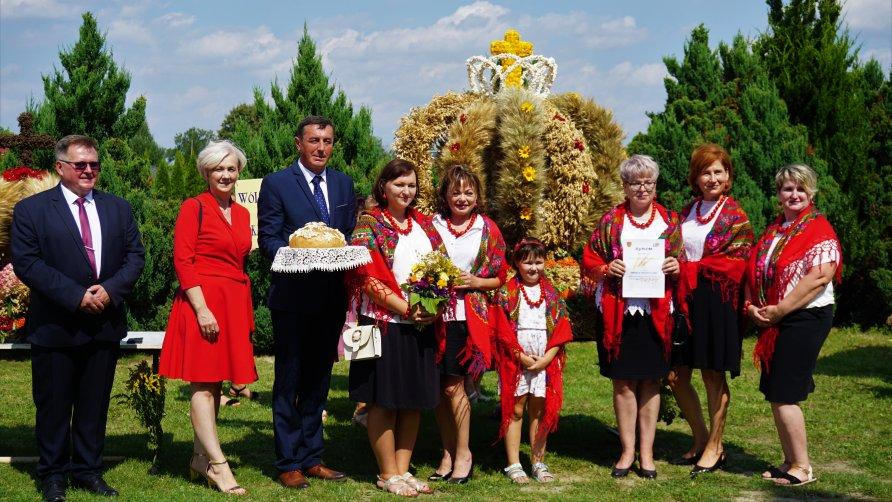 Zdjęcie przedstawia grupę osób mężczyzn i kobiet z wieńcem dożynkowym. Kilka kobiet ubranych jest w stroje ludowe. Jedna z osób (Wójt Gminy Lubartów) trzyma w rękach chleb.