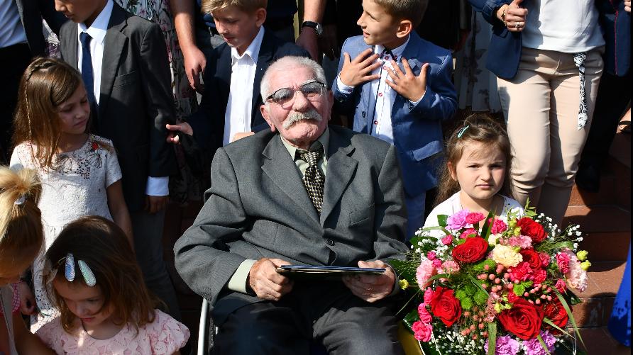 Zdjęcie przedstawia starszego mężczyznę na wózku inwalidzkim trzymającego w rękach list gratulacyjny. Otoczony jest przez uśmiechnięte dzieci i osoby dorosłe.