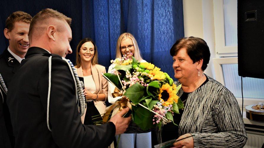 Zdjęcie przestawia Panią Dyrektor przyjmującą kwiaty od strażaków