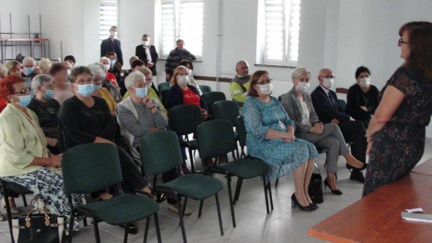 Zdjęcie przedstawia siedzące osoby oraz osobę przemawiającą do nich
