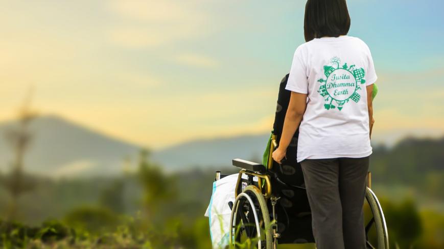 Obraz przedstawia osobę prowadzącą wózek inwalidzki