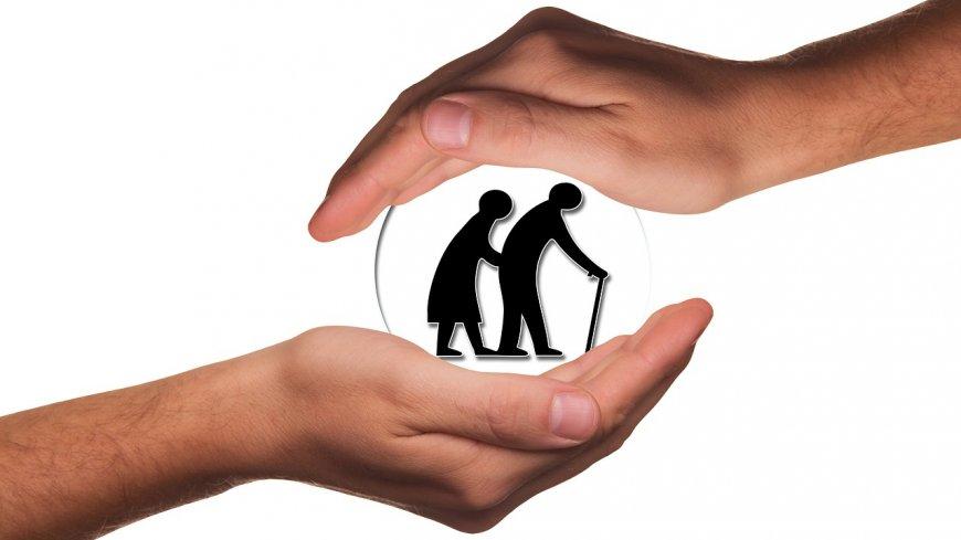 Obraz przedstawia ręce otulające seniorów